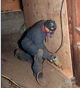 THIS PHOTO SHOWS A CONTRACTOR NAILING THE REVERSE BLOCK INTO THE MUDSILL. THE PLYWOOD WAS NAILED TO THE REVERSE BLOCK BEFORE IT WAS PLACED IN THIS POSITION