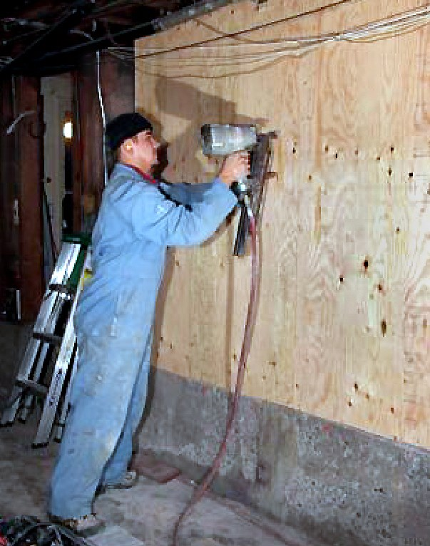 TECHNICIAN NAILING PLYWOOD WHICH IS THE FINAL STAGE OF BUILDING A SHEAR WALL